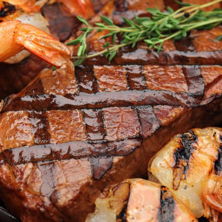 Juicy BBQ sirloin steak with grilled shrimps - Surf and Turf